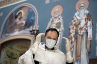 In this June 2, 2020 photo, Father Vasily Gelevan wearing a face mask and gloves prepares to conduct a service at the Church of the Annunciation of the Holy Virgin in Sokolniki in Moscow, Russia. (AP Photo/Alexander Zemlianichenko)