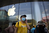 People wearing face masks to protect against the new coronavirus stand outside of an Apple store in Beijing, Saturday, June 6, 2020.  (AP Photo/Mark Schiefelbein)