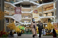 Shoppers wearing face mask walk through a shopping mall in downtown Kuala Lumpur, Malaysia, on Sunday, June 7, 2020. (AP Photo/Vincent Thian)