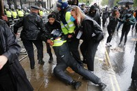 A police officer who was injured when falling of a horse during scuffles with demonstrators at Downing Street during a Black Lives Matter march in London, Saturday, June 6, 2020, is dragged by colleagues, as people protest against the killing of George Floyd by police officers in Minneapolis, USA. (AP Photo/Frank Augstein)