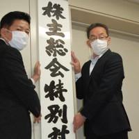 株主総会特別対策本部の看板を設置する大庭英次・組織犯罪対策課長(左)ら