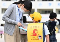 A teacher checks a student's temperature and other items on a health checklist at the entrance of a school in Kitakyushu's Kokuraminami Ward in southwestern Japan on June 1, 2020. (Mainichi/Noriko Tokuno)