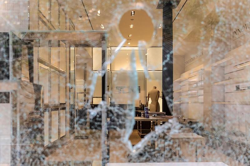 抗議活動で割られた店舗のガラス (Bloomberg)