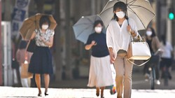 猛暑日の中、日傘を差して歩く人たち。コロナ禍からの経済復興には温暖化防止の政策も求められている=福岡県久留米市で2020年6月8日、徳野仁子撮影