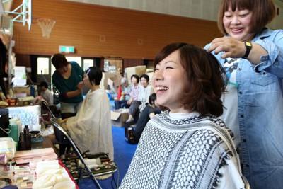 プロのヘアメークアーティスト、ネイリスト、モデルらが小学校前の仮設住宅を訪れ、住民に髪や爪のセットを行った。笑顔がこぼれる女性は「震災以来、髪をセットしてもらったのは2回目。化粧もしてもらい自然と笑顔になります」=岩手県陸前高田市で2011年6月19日午前10時40分、武市公孝撮影