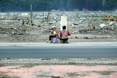 東北地方が梅雨入りし、傘を手に臨時バスを待つ女性たち。2人は初対面だったが、震災当時の話を語り合っていた=岩手県大槌町で2011年6月21日午後3時9分、小川昌宏撮影