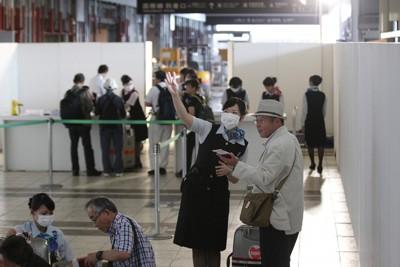 震災後、初めての国際便が就航し、投光機に照らされた仮設のチェックインカウンターで搭乗手続きを行う乗客=仙台空港で2011年6月23日午後3時8分、尾籠章裕撮影