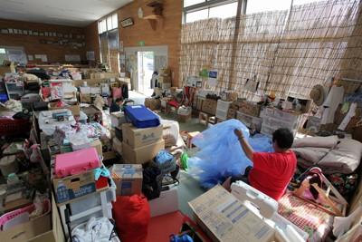 梅雨の中休みとなり、宮城県内も各地で気温が30度以上の真夏日となった。避難所となっている高校の柔道場では、よしずで日よけした部屋の中で入り口に蚊帳をつけるため、避難者の女性が一人で作業をしていた=宮城県南三陸町の志津川高で2011年6月29日午後2時47分、手塚耕一郎撮影