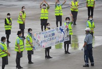 ANA group employees hold a banner as they see off a Boeing 737-500, affectionately called