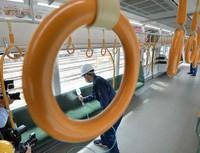 Workers are seen disinfecting a railway car on the JR Osaka Loop Line in Osaka's Joto Ward. (Mainichi/Ryoichi Mochizuki)