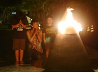 A family prays in front of a flame at the