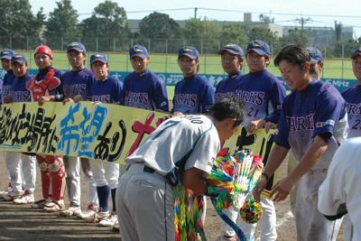 試合終了後、日本製紙石巻の西尾主将(手前)に千羽鶴を贈る熊本ゴールデンラークスの山内主将(右端)=熊本県八代市の県営八代球場で2011年午後3時49分、田内隆弘撮影