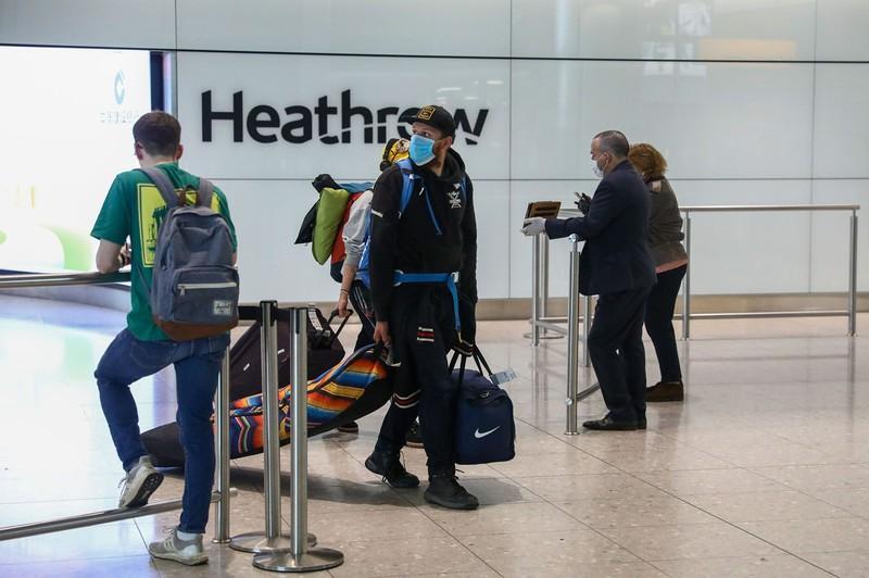 ロンドンのヒースロー空港に到着したマスクをつけた乗客(Bloomberg)