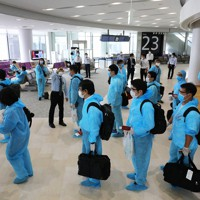 防護服を着てベトナム行きの臨時便に搭乗する乗客=成田空港で2020年6月25日午前11時1分、長谷川直亮撮影