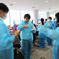 新型コロナウイルスの感染拡大防止のために実施されている出入国制限が緩和され、ベトナム行きの臨時便の搭乗前に防護服を着る乗客=成田空港で2020年6月25日午前10時39分、長谷川直亮撮影