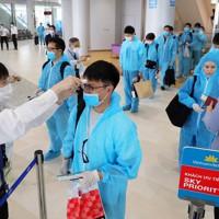 防護服を着てベトナム行きの臨時便に搭乗する乗客=成田空港で2020年6月25日午前11時、長谷川直亮撮影