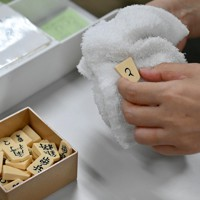 対局ごとに消毒液をしみこませたタオルで拭き取られる駒=大阪市福島区で2020年6月13日、山田尚弘撮影