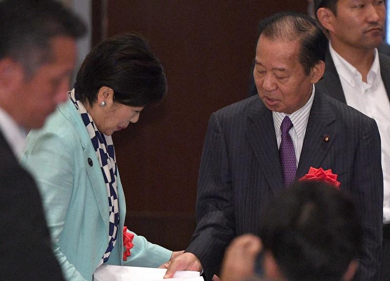 小池百合子東京都知事の支援団体が開いたセミナーで講演した自民党の二階俊博幹事長(右)から資料を手渡される小池知事(左)=東京都新宿区で2019年(令和元年)8月20日、丸山博撮影