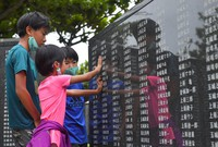 Children trace relatives' names engraved on the