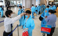 Passengers wearing hazmat suits are seen getting checked before boarding a special flight to Vietnam, at Narita International Airport, east of Tokyo, on June 25, 2020. (Mainichi/Naoaki Hasegawa)