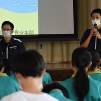 100人の中学生を前に海の事故を防ぐための対策を話す保安官=新潟市北区の市立松浜中学校で