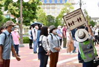 A cast member is seen with a sign urging people to maintain social distancing during a press event at Tokyo Disneyland in Urayasu, Chiba Prefecture, on June 29, 2020, ahead of the theme park's July 1 reopening. (Mainichi/Takehiko Onishi)
