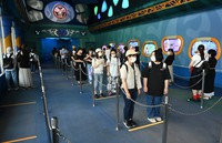 Staff members playing the role of visitors form a line while maintaining social distancing at an attraction at Tokyo Disneyland in Urayasu, Chiba Prefecture, on June 29, 2020, during a press event ahead of the theme park's July 1 reopening. (Mainichi/Takehiko Onishi)