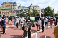 Staff members playing the role of visitors form a line while maintaining social distancing in front of the entrance to Tokyo Disneyland in Urayasu, Chiba Prefecture, on June 29, 2020, during a press event ahead of the theme park's July 1 reopening. (Mainichi/Takehiko Onishi)