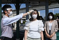 A staff member playing the role of a visitor is seen getting their temperature checked in front of the entrance to Tokyo Disneyland in Urayasu, Chiba Prefecture, on June 29, 2020, ahead of the theme park's July 1 reopening. (Mainichi/Takehiko Onishi)