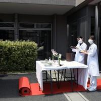 「KITCHENCAR′S CONNECT(キッチンカーズ コネクト)」の第2回はグリルトウキョウがローストビーフとグリルチキンのコンビ弁当を届けた。レッドカーペットを歩き弁当を受け取った人たちは笑顔を見せた=埼玉県所沢市の所沢ロイヤル病院で2020年5月28日、竹内紀臣撮影