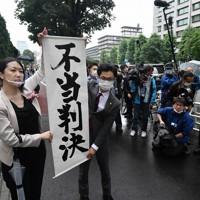 東京地裁の判決後、「不当判決」と書かれた旗を掲げる原告の弁護士ら=東京都千代田区で2020年6月30日午後2時12分、宮間俊樹撮影
