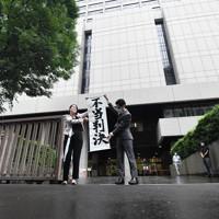 東京地裁の判決後、「不当判決」と書かれた旗を掲げる原告の弁護士=東京都千代田区で2020年6月30日午後2時10分、宮間俊樹撮影