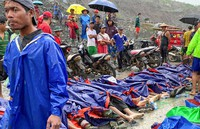 People gather near the bodies of victims of a landslide near a jade mining area in Hpakant, Kachine state, northern Myanmar, on July 2, 2020. (AP Photo/Zaw Moe Htet)