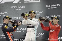 In this Dec. 1, 2019 file photo, Mercedes driver Lewis Hamilton of Britain, center, celebrates on the podium after winning the Emirates Formula One Grand Prix as Red Bull driver Max Verstappen of the Netherland's, left, and Ferrari driver Charles Leclerc of Monaco, look on, at the Yas Marina racetrack in Abu Dhabi, United Arab Emirates. (AP Photo/Luca Bruno)