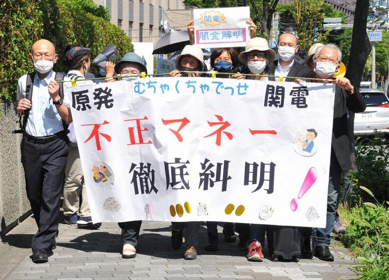 関西電力の役員らに損害賠償を求めて提訴するため、大阪地裁へ向かう株主ら=大阪市北区で2020年6月23日午後2時37分、服部陽撮影