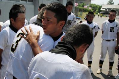 第93回全国高校野球選手権宮城大会で、津波で校舎が損壊した気仙沼向洋は登米に4―5で敗れた。川村監督(中央)は選手たちを抱き寄せ、感謝の言葉を伝えた=宮城県美里町の南郷球場で2011年7月12日、岸本悠撮影
