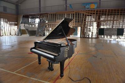津波で破壊された体育館の中で、再び生徒たちと一緒に音を響かせる時を待つグランドピアノ=福島県いわき市の豊間中で2011年7月8日、小林努撮影