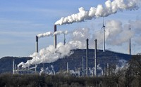 In this Jan. 16, 2020 file photo an uniper coal-fired power plant and BP refinery steam beside a wind generator in Gelsenkirchen, Germany. (AP Photo/Martin Meissner)