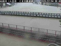 In this photo provided by the Ministry of Land, Infrastructure, Transport and Tourism, water reaches a railway bridge in the city of Hitoyoshi in the southwestern Japan prefecture of Kumamoto after record rainfall raised the level of the Kuma River.