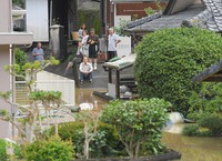 People who evacuated to a road after water from the Kuma River flooded a residential area are seen in the city of Yatsushiro, in the southwestern Japan prefecture of Kumamoto at 11:22 a.m. on July 4, 2020. (Mainichi/Toyokazu Tsumura)