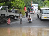 People are seen near a road flooded with water from the Kuma River in the city of Yatsushiro, in the southwestern Japan prefecture of Kumamoto at 11:01 a.m. on July 4, 2020. (Mainichi/Toyokazu Tsumura)
