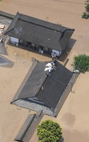 People escaping floodwaters sit on the roof of a home in the city of Hitoyoshi, in the southwestern Japan prefecture of Kumamoto at 11:49 a.m. on July 4, 2020. (Mainichi/Kimiya Tanabe)