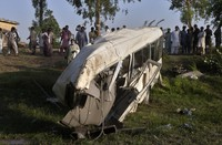 Local residents gather beside the wreckage of a bus close to a railway track following a train and bus accident, in Farooq Abad in Sheikhupura district, Pakistan, on uly 3, 2020. (AP Photo/K.M. Chaudary)