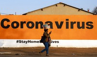 In this June 19, 2020 photo, a woman wearing a face mask passes a coronavirus safety awareness billboard. South Africa's reported coronavirus are surging. (AP Photo/Themba Hadebe)