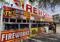 In this July 2, 2013 file photo, a family purchases fireworks at a TNT Fireworks stand in the City of Monterey Park, California. (AP Photo/Nick Ut)