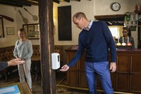 Britain's Prince William uses hand sanitizer as he enters The Rose and Crown pub in Snettisham, the U.K., on July 3, 2020. English pubs are among the businesses that are allowed to welcome guests with some anti-virus precautions from Saturday July 4, as the coronavirus restrictions are eased. (Aaron Chown/Pool via AP)