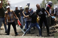 Palestinian demonstrators hurl stones at Israeli troops during a protest against Israel's plan to annex parts of the West Bank and Trump's Mideast initiative, in the West Bank village of Kufr Qaddumm, on July 3, 2020. (AP Photo/Majdi Mohammed)