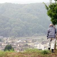 河川の氾濫によって破壊された自宅周辺の景色を見つめる人たち=熊本県球磨村で2020年7月5日午前7時23分、幾島健太郎撮影