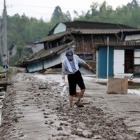 河川の氾濫で土砂に覆われた道路を慎重に歩く男性=熊本県球磨村で2020年7月5日午前8時27分、幾島健太郎撮影