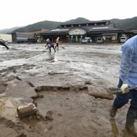 道の駅に貯まった大量の土砂を片付ける人たち=熊本県芦北町で2020年7月5日午後2時45分、矢頭智剛撮影